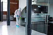 Cleaner wearing protective face mask and overalls disinfecting office and furniture