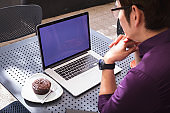 Asian businessman using laptop with blank screen sitting at table in cafe