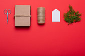 Composition of scissors, box, rope, card and tree branches on red background