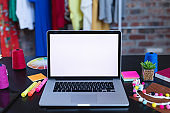 Laptop with copy space on screen lying on desk full of designers accessories