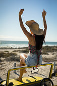 Caucasian woman sitting on beach buggy by the sea wearing straw hat looking toward sea with hands up