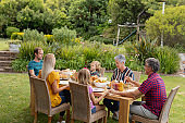 Caucasian three generation family holding hands saying grace before eating meal together in garden