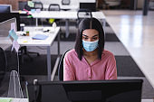 Mixed race businesswoman sitting in office in front of computer wearing face mask