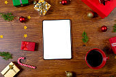 Composition of tablet with copy space and christmas decorations on wooden background