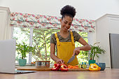 Mixed race woman cutting vegetables using laptop and smiling in a kitchen