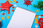 Composition of notebook with copy space and christmas decorations on blue background