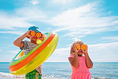 happy kids with fresh oranges and floatie on beach , concept of a healthy diet, vitamins, lifestyle