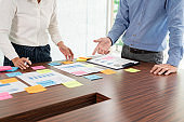 Creative group of business people brainstorming use sticky notes picking to share idea on table decision Choosing Concept for developing plan in business conference room