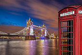 Tower Bridge with red phone booth at night in London, England, UK