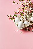 White eggs and twigs with flowers on pink background