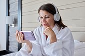 Woman in bathrobe and headphones looking at smartphone screen, sitting in bed