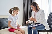 Woman social worker talking to girl. Child psychology, mental health