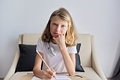 Portrait of 10 year old student child girl sitting at desk with pencil in her hand