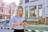 Outdoor young business woman with smartphone looking at wrist watch