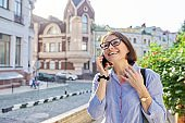 Mature business woman talking on cell phone walking down city street