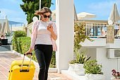 Tourism, travel, woman with suitcase walking along road of hotel complex