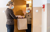 Female volunteer delivering bags with shopping to elderly woman during coronavirus pandemic