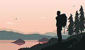 Backpacker by lake - Man standing in beautiful landscape watching the view with backpack
