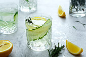 Healthy drink. Lemonade with fresh cucumbers, lemons and rosemary. Bright background. Summer drinks.
