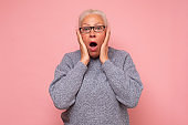 Stressed surprised old mature woman looking at camera worried about facial wrinkles.