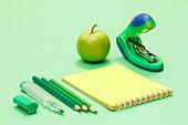 School supplies. Color pencils, notebook, apple and stapler.