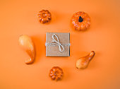 Gift box and pumpkins on an orange background