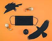 Black mask, pumpkins and paper crow on orange