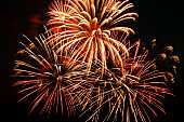 Festive fireworks in the sky for a holiday. Bright multi-colored salute on a black background. Place for text.