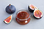 Fig jam in the glass jar on the gray cement  background