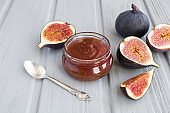Fig jam in the glass jar on the gray wooden background