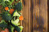 Frozen vegetables in the cutting board on the brown  wooden background. Top view. Copy space.
