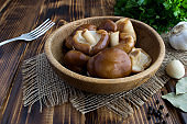 Marinated mushrooms shiitake in the brown plate on the  rustic wooden background