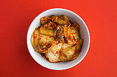 Kimchi in the white plate on the red  background