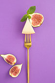 Slice of cheese and figs on a gold fork on the purple background. Close-up.