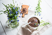 Flax Seeds and Blue Flax Flowers Bunch on White Wooden Table