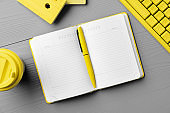 Yellow notepad on gray wooden background top view