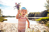 Happy beautiful cute child girl with flower bouquet walking on beach in sunny summer day