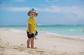 Cute baby boy playing with beach toys on tropical beach