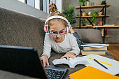 Girl in the glasses studying online from home using laptop