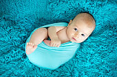 Cute three months old baby boy in blue wrap, lying on a blue blanket, looking curiously