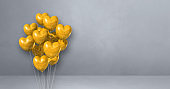 Yellow heart shape balloons bunch on a grey wall background. Horizontal banner.