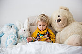 Beautiful child, toddler boy, reading book and playing with it, creative knowledge shot with book