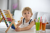 Sweet toddler child, blond boy, learning math at home with colorful abacus