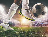 Close up of a soccer scene with player in a white uniform kicking the ball with power