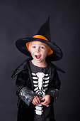 Child, dressed for Halloween, playing at home, isolated image on black