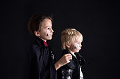 Children. brothers, dressed for Halloween, playing at home, isolated image