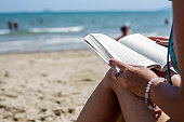 Woman reading a book on the beach, blurred background. Summer leisure on the beach