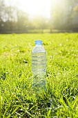 Transparent bottle of fresh water standing on a green lawn outside on a sunny day. Single object, no people. Vertical photo