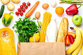 Vegetables, fruits assortment with shopping bag and bottle of milk on white background. Vegetarian healthy food concept. Food and grocery shopping