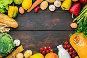 Vegetables, fruits assortment frame on dark wooden table. Vegetarian healthy food concept. Food and grocery shopping. Free space